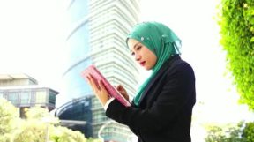 stock-footage-portrait-of-young-beautiful-muslim-wearing-hijab-using-tablet-computer-outdoors-in-the-city
